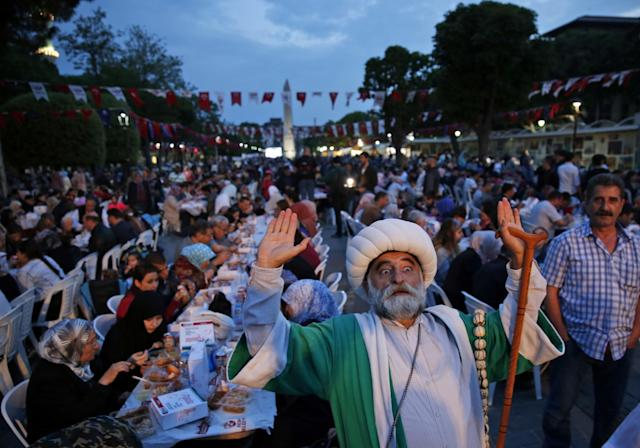 <p>A man in Ottoman attire poses for pictures as people break their fast in the historic Sultanahmet district of Istanbul, Turkey, May 27, 2017. (AP Photo/Lefteris Pitarakis) </p>