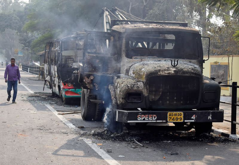 A man walks past damaged vehicles that were set on fire by demonstrators, during a protest after India's parliament passed Citizenship Amendment Bill, in Guwahati