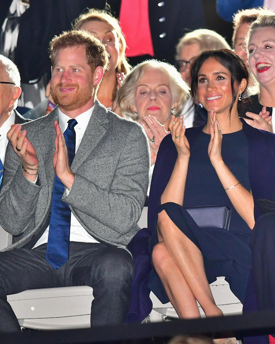 <p>Meghan rewore a Stella McCartney navy blue cape dress for the Invictus Games Opening Ceremony. She wore a Gillian Anderson swing coat over the dress, and held a satin Dior clutch. <em>[Photo: Getty]</em> </p>