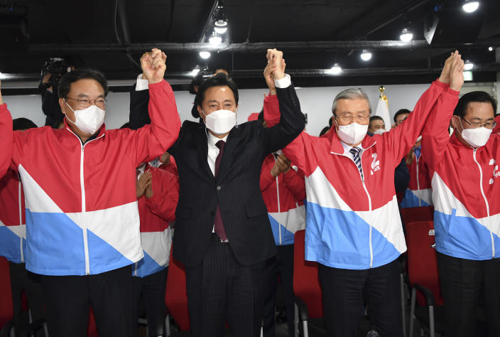 Oh Se-hoon, candidate of the main opposition People Power Party, celebrates with party members while watch monitors broadcasting the results of exit polls for the Seoul mayoral by-election at the party's headquarters Wednesday, April 7, 2021, in Seoul, South Korea. (Song Kyung-seok/Pool Photo via AP)