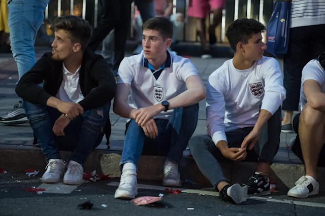 <p>A group of England supporters in Birmingham sit on the pavement minutes after the heartbreaking defeat. (SWNS) </p>