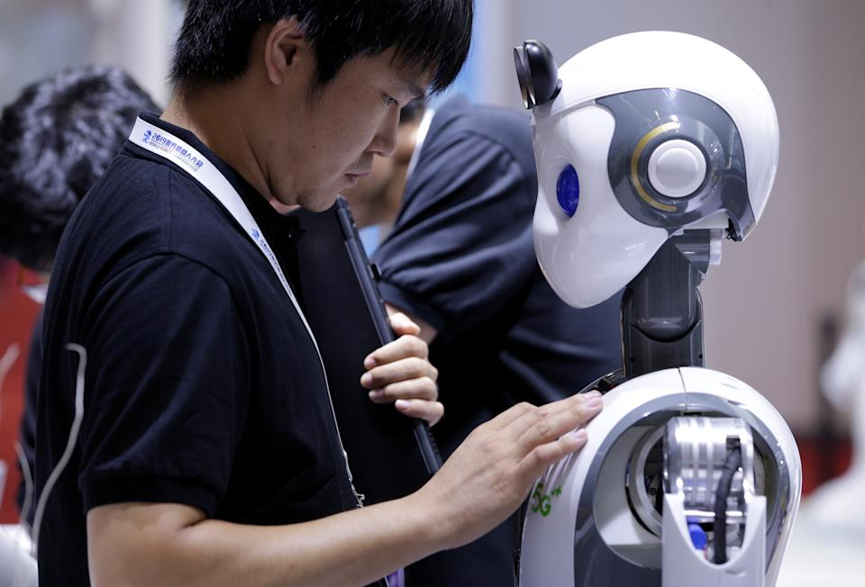 An engineer sets up a CloudMinds robot with a 5G sign before a performance at the World Robot Conference (WRC) in Beijing, China August 20, 2019. REUTERS/Jason Lee