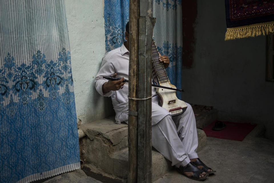 An Afghan musician poses for a portrait with his dilruba in Kabul, Afghanistan, Saturday, Sept. 18, 2021. About a month after the Taliban seized power in Afghanistan, the music is starting to go quiet. The last time that the militant group ruled the country, in the late 1990s, it outright banned music. (AP Photo/Bernat Armangue)