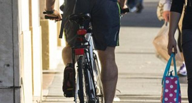 A cyclist is pictured riding on a footpath.