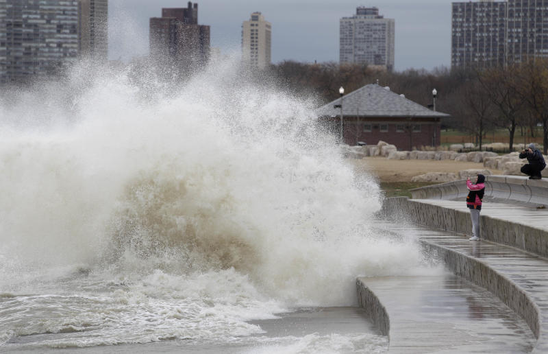 Onlookers take photos as strong waves created by superstorm Sandy crash against the Lake Michigan waterfront, Tuesday, Oct. 30, 2012, on the south side of Chicago. Strong winds from the outer edge of superstorm Sandy are ripping up near-record high waves on Lake Michigan. (AP Photo/M. Spencer Green)