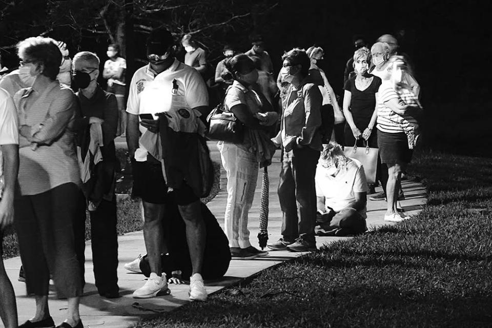 Voters wait in the dark before polls open in Boca Raton on Oct. 19, 2020, the first day of early voting in Florida.