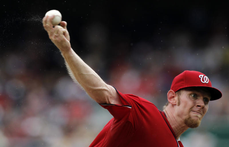 Moisture flies off the the hand of Washington Nationals starting pitcher Stephen Strasburg during the third inning of a baseball game in the rain against the St. Louis Cardinals at Nationals Park, Sunday, Sept. 2, 2012, in Washington. (AP Photo/Alex Brandon)