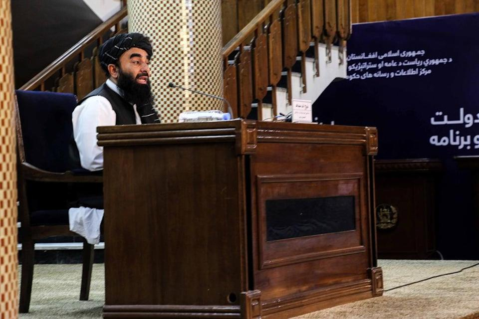 Zabhiullah Mujahid, the Taliban spokesperson, talks with journalists as he announces the interim government (EPA)