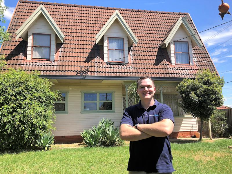 Eddie Dilleen in front of a recently renovated house that he purchased.