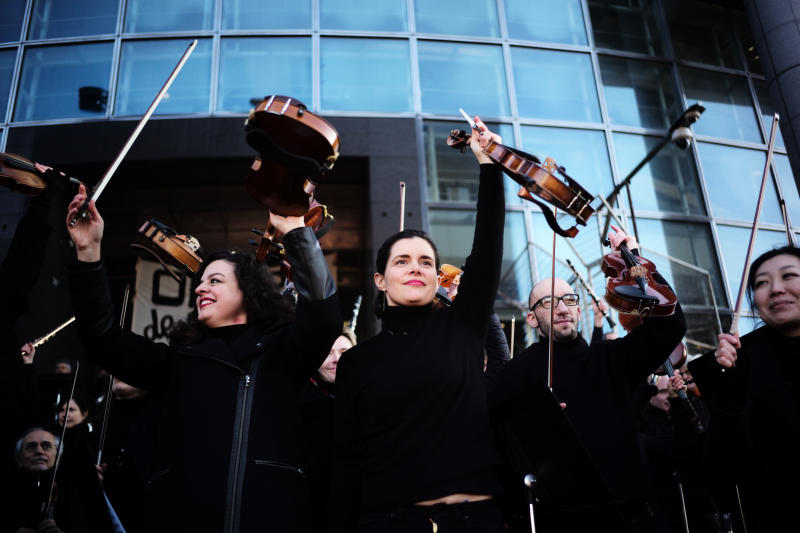 Striking musicians of the Paris Opera house hold their violins after performing outside the Bastille Opera house Tuesday, Dec. 31, 2019 in Paris. (AP Photo/Kamil Zihnioglu)