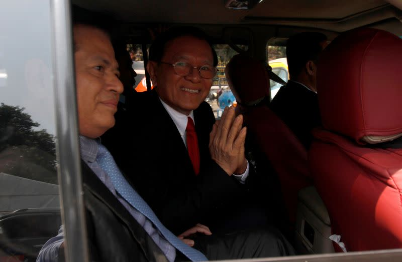 Cambodian opposition leader Kem Sokha greets as he leaves the Municipal Court of Phnom Penh