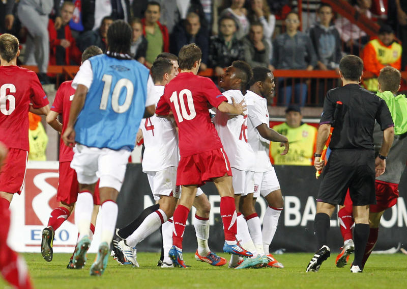 Serbian players, in red, clash with England players, in white, during their 2013 UEFA European Under-21 Championship play-off, second leg match between Serbia and England, in Krusevac, Serbia, Tuesday, Oct .16, 2012. Serbia is facing UEFA sanctions after England complained that its Under-21s team was racially abused and missiles were hurled onto the pitch. (AP Photo/Miroslav Todorovic)