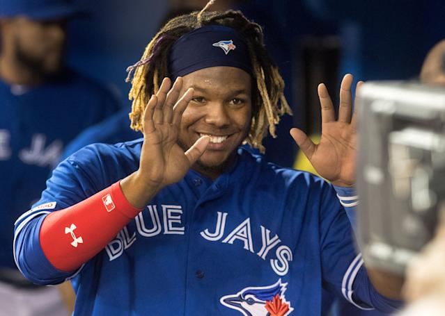 Toronto Blue Jays' Vladimir Guerrero Jr. smiles for a television camera looking into the dugout in the sixth inning of a baseball game against the Oakland Athletics in Toronto, Saturday April 27, 2019. (AP Photo)
