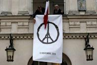 """Municipal employees deploy a banner with the drawing """"Peace for Paris"""" by French artist Jean Jullien as people observe a minute of silence at the city hall in Nantes, France, to pay tribute to the victims of the series of deadly attacks on Friday in Paris, November 16, 2015. REUTERS/Stephane Mahe"""