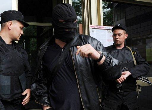 A man wearing a balaclava walks past two policemen holding submachine guns as they guard an entrance to the house of Alexei Navalny, an opposition leader and a popular anti-corruption blogger, in Moscow on June 11, 2012. Police armed with assault rifles raided the homes of Russia's top protest leaders on June 11 in a show of force on the eve of a mass Moscow rally against President Vladimir Putin