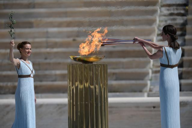 Greek actress Xanthi Georgiou dressed as an ancient Greek high priestess lights the Olympic torch as choreographer Artemis Ignatiou looks on during the olympic flame handover ceremony for the 2020 Tokyo Summer Olympics, in Athens, Thursday March 19, 2020. (Aris Messinis/Pool via AP)