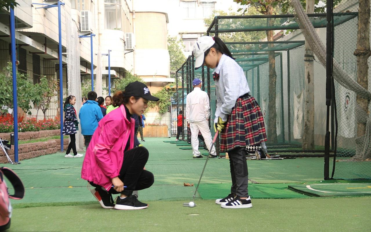 "Golf was banned in China, after being branded a ""sport for millionaires"", but is now being made compulsory in schools to teach children etiquette and instill good behaviour. China has a longstanding love-hate relationship with golf, which has been vilified by the country's Communist rulers but enjoyed by local officials. Labelled a ""sport for millionaires"" by Mao Tse-tung after he assumed power in 1949, a current war on golf is seen as part of a wider campaign by Xi Jinping, the Chinese president, on corruption and excess. However, China has some of the best golf courses in the world and an exciting crop of teenage players who have been making an impact on major tournaments.   The rising profile of Chinese players and growing access to driving ranges and courses has helped develop interest in the sport among more affluent families from urban areas. A golfer tees off at Huatang International Golf Club in Beijing Credit: National Geographic Creative / Alamy Stock Photo A state school in the commercial hub of Shanghai last year became the first to provide compulsory lessons, with the headmaster saying it provided seven- and eight-year-old pupils with ""an important social skill for them to step towards international society"". And now schools outside China's richer, cosmopolitan cities – where parents may have never heard of Tiger Woods or Rory McIlroy – are beginning to provide compulsory classes for students. Jingwulu Primary School, in Jinan, in the eastern Shandong province, introduced the sport to ""foster children's strong determination, self-discipline and manners,"" headmistress Ji Yankun said. ""I don't think I am being over dramatic in calling it a gentleman's sport, as there is so much good etiquette involved,"" she told The Telegraph. The school has installed practice nets in its grounds and drafted in coaches from Shandong Gold Golf Club to provide compulsory training to nine-year-old pupils. The golf club is also consulting with four other schools to roll out the training across the province.  ""Many children have fallen in love with the sport, which has been called 'the green opium',"" said Shandong Gold's Jiang Chunqiu, using a phrase which is often used in China to portray golf as highly enjoyable, but a dangerous foreign import. ""It is an elegant sport, and we want to train the child's self-discipline to make them a gentleman or gentlewomen."" She said all children must first learn the ""manner requirements"" before they begin their lessons. ""They must apologise if they are late – even if it is less than five minutes,"" she said. ""And we demand that they behave themselves at all times during the competition."" Building golf courses has been banned, but this hasn't dampened enthusiasm  Credit:  Die Bildagentur der Fotografen GmbH / Alamy Stock Photo The Chinese school system is heavily focused on academic learning and pushing pupils through high-pressured exams. The priority for parents has traditionally been for their children to achieve top marks and attend a prestigious foreign university. However, attitudes are changing, and many now seek to encourage their children to do activities that are perceived to influence temperament and behavior, such as music, ballet or golf. Parents in China often pay for their children to attend expensive extra-curricular lessons in sports or the arts. Despite growing interest in golf among Chinese, the government has sought to curtail the number of golf courses being built in China, banning the construction of new courses in 2004. But numbers have increased from less than 200 to almost 700 since the ban because of growing demand from the wealthy and lower level Communist officials. Local governments have also encouraged the building of clubs to boost tourism and increase development opportunities. Additional reporting by Christine Wei"