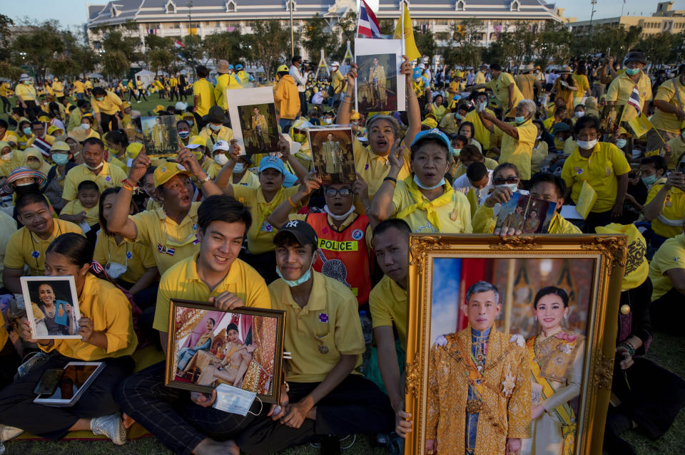 Supporters of Thai monarch display images the royal family ahead of the arrival of King Maha Vajiralongkorn and Queen Suthida to participate in a candle lighting ceremony to mark birth anniversary of late King Bhumibol Adulyadej at Sanam Luang ceremonial ground in Bangkok, Thailand, Saturday, Dec. 5, 2020. (AP Photo/Gemunu Amarasinghe)