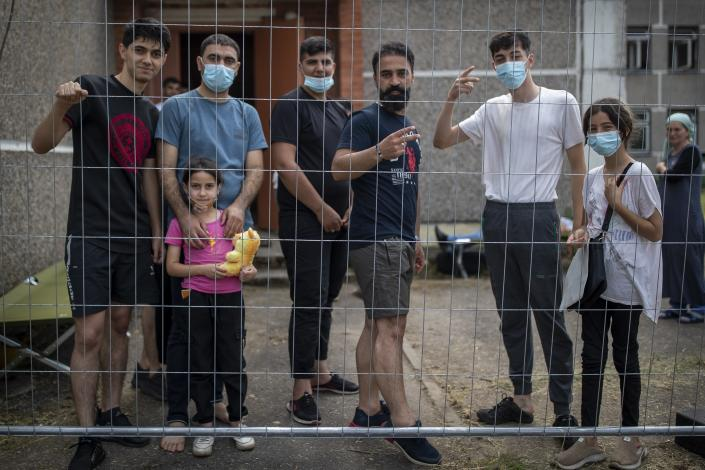 Migrants from Iraq speak to journalists through a fence at the refugee camp in the village of Verebiejai, some 145km (99,1 miles) south from Vilnius, Lithuania, Sunday, July 11, 2021. Migrants at the school in the village of Verebiejai, about 140 kilometers (87 miles) from Vilnius, haven't been allowed to leave the premises and are under close police surveillance. Some have tested positive for COVID-19 and have been isolated in the building. (AP Photo/Mindaugas Kulbis)