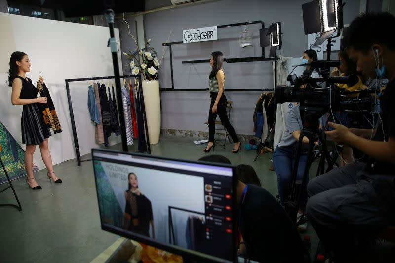 Staff members display clothing items during a live-streaming session for Canton Fair in Guangzhou