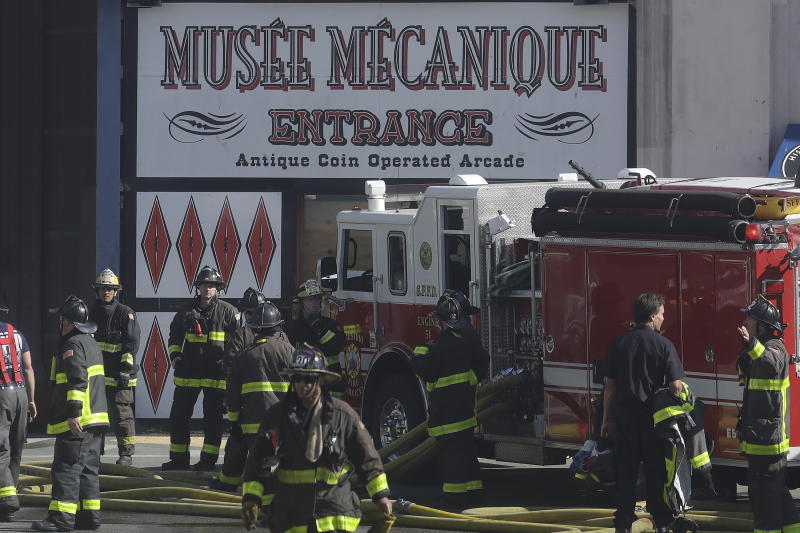 Fire officials work in front of a sign for Musee Mecanique after a fire broke out before dawn at Fisherman's Wharf in San Francisco, Saturday, May 23, 2020. Fire officials said no injuries have been reported Saturday morning and firefighters are making multiple searches to ensure no one was inside the building on Pier 45. (AP Photo/Jeff Chiu)