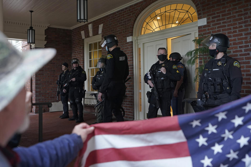 FILE - In this Jan. 6, 2021 file photo, protesters square off with law enforcement officers on the front porch of the Governor's Mansion after a group of people got through a perimeter fence at the Capitol in Olympia, Wash. Statehouses where Trump loyalists have rallied since the Nov. 3 election are heightening security after the storming of the U.S. Capitol this week. Police agencies in a number of states are monitoring threats of violence as legislatures return to session and as the nation prepares for the inauguration of President-elect Joe Biden. (AP Photo/Ted S. Warren, File)