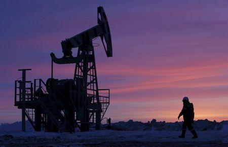 FILE PHOTO:  A worker walks past a pump jack on an oil field owned by Bashneft in Bashkortostan