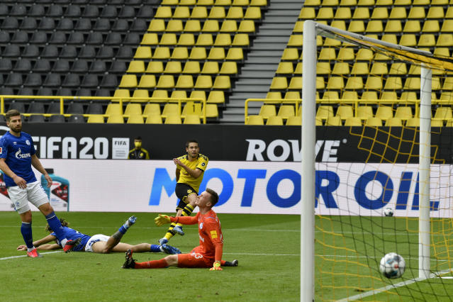 Dortmund's Raphael Guerreiro, background center, scores his side's second goal during the German Bundesliga soccer match between Borussia Dortmund and Schalke 04 in Dortmund, Germany, Saturday, May 16, 2020. The German Bundesliga becomes the world's first major soccer league to resume after a two-month suspension because of the coronavirus pandemic. (AP Photo/Martin Meissner, Pool)