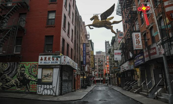 """A street in New York's Chinatown is empty, the result of citywide restrictions calling for people to stay indoors and maintain social distancing in an effort to curb the spread of COVID-19, Saturday March 28, 2020, in New York. President Donald Trump says he is considering a quarantine affecting residents of the state and neighboring New Jersey and Connecticut amid the coronavirus outbreak, but New York Gov. Andrew Cuomo said that roping off states would amount to """"a federal declaration of war."""" (AP Photo/Bebeto Matthews)"""