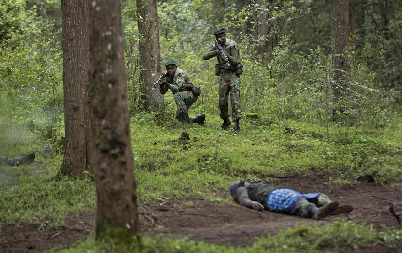 FILE - In this Thursday, Dec. 5, 2013 file photo, rangers of the Kenya Wildlife Service and Kenya Forest Service shoot at a colleague playing the role of a poacher as they stage a demonstration of the skills they have learned over the last few days of joint anti-poaching training with Britain's 3rd Battalion, The Parachute Regiment, in the forest near Nanyuki, Kenya. Famed scientist and founding former chairman of the Kenya Wildlife Service (KWS) Richard Leakey is urging Kenya's president to invoke emergency measures to protect the country's elephants and rhinos and said Wednesday, March 19, 2014 that the KWS had been infiltrated by people enriching themselves off poaching, that poaching ring leaders were known, but that the government has taken no action. (AP Photo/Ben Curtis, File)