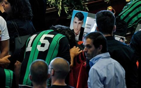 Relatives of an Albanian victim of the collapsed Morandi highway bridge, mourn near the coffin, prior to the start of the funeral service, in Genoa