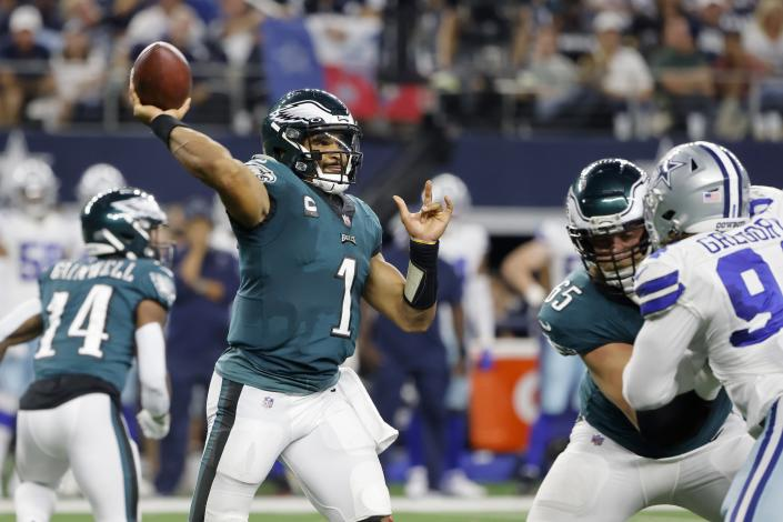 Philadelphia Eagles quarterback Jalen Hurts (1) throws a pass as offensive tackle Lane Johnson (65) defends against pressure from Dallas Cowboys defensive end Randy Gregory (94) in the second half of an NFL football game in Arlington, Texas, Monday, Sept. 27, 2021. (AP Photo/Michael Ainsworth)