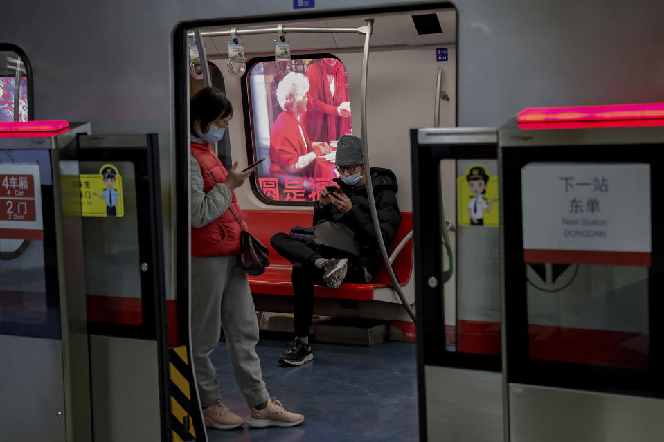 Commuters wearing face masks to help curb the spread of the coronavirus browse their smartphones inside a subway train in Beijing Wednesday, Feb. 10, 2021. China's internet watchdog is cracking down further on online speech, issuing a new requirement that bloggers and influencers have a license before they can publish on certain topics. The rule from the Cyberspace Administration of China that goes into effect later this month is shrinking an already highly limited space for discourse amid heavy censorship of sensitive topics and any perceived criticism of the ruling Communist Party. (AP Photo/Andy Wong)