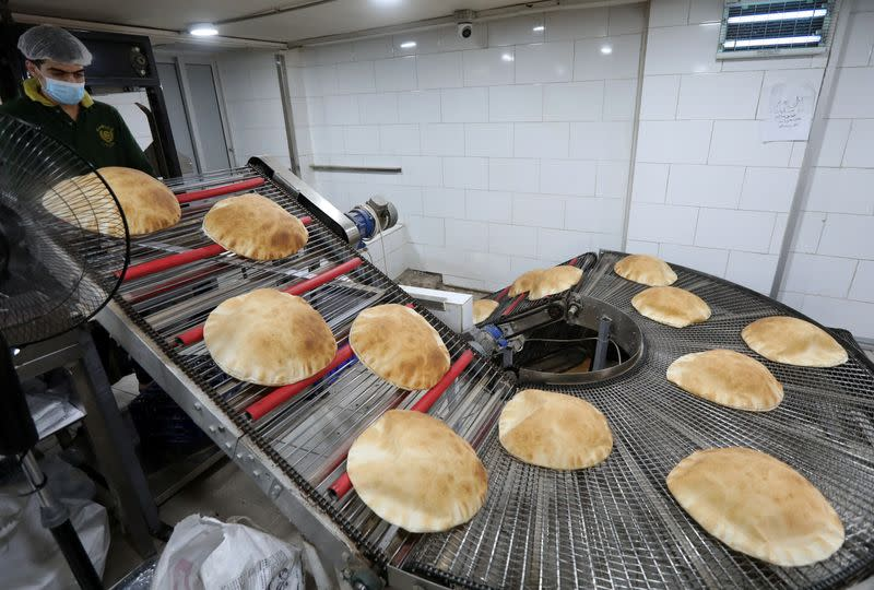 A worker stands near freshly baked bread at a bakery in Beirut