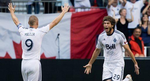 Vancouver Whitecaps' Tom Heinemann, left, celebrates his game-tying goal with teammate Kenny Miller, of Scotland, during the second half of an MLS soccer game against Chivas USA, Sunday, Sept. 1, 2013 in Vancouver, British Columbia. (AP Photo/The Canadian Press, Darryl Dick)