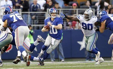 New York Giants quarterback Manning scrambles from the pocket as guard Snee blocks and nose tackle Ratliff pursues in the first half of their NFL football game in Arlington