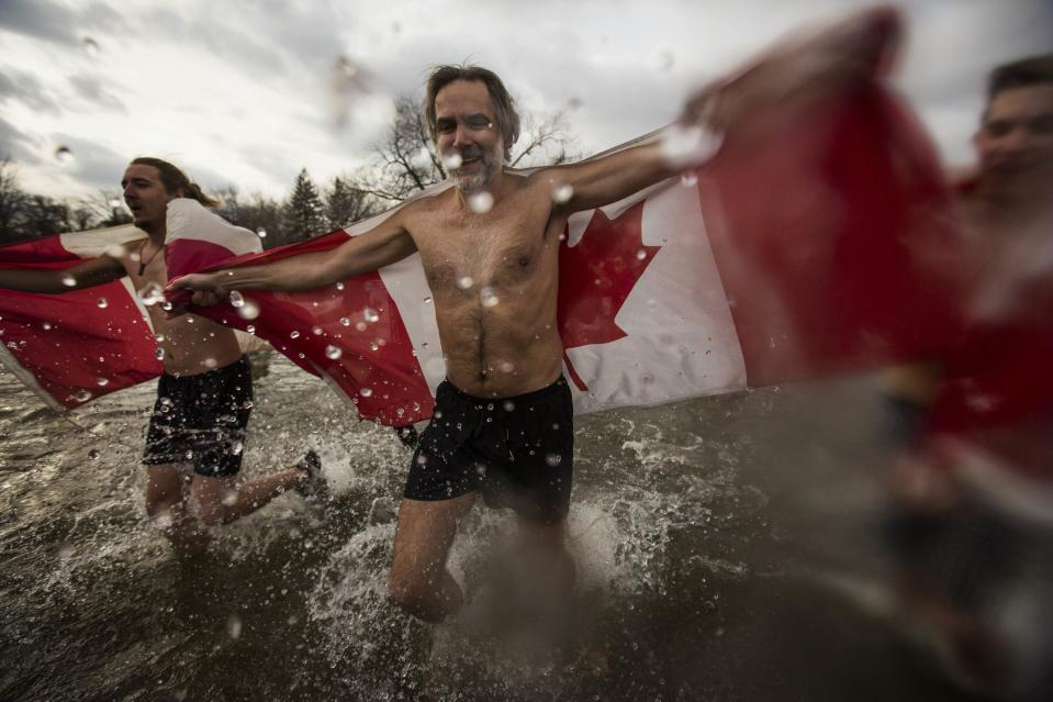 """Participants take part in Courage Polar Bear Dip at Coronation Park in Oakville, January 1, 2015. This year's edition of the Courage Polar Bear Dip, in which hundreds of participants ran into Lake Ontario in subfreezing temperatures, will raise money for the """"Rwanda: Right to Clean Water"""" project. REUTERS/Mark Blinch (CANADA - Tags: SOCIETY)"""