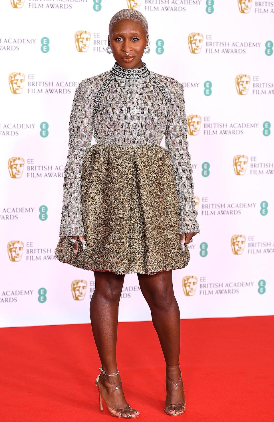 <p>brings the bling in a shimmery gold long-sleeve Louis Vuitton mini dress. </p>