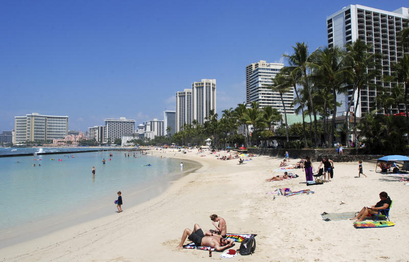 FILE - In this Monday, March 13, 2017 file photo, people relax on the beach in Waikiki in Honolulu. A federal judge in Hawaii is hearing arguments on whether to extend his temporary order blocking President Donald Trump's revised travel ban. A hearing in Honolulu is set for Wednesday, March 29, 2017. (AP Photo/Caleb Jones, File)
