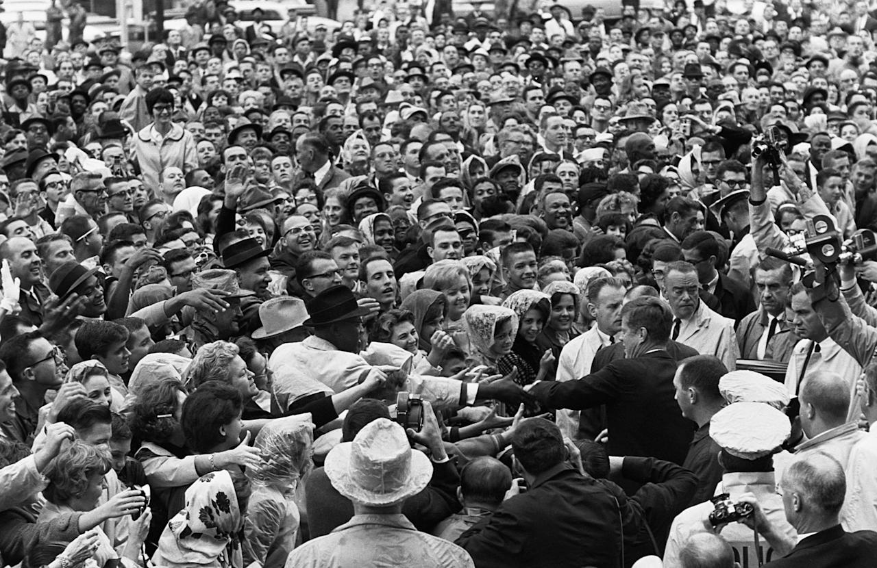 <p>President Kennedy shakes hands with people in a crowd in Ft. Worth, Texas, on the day of his assassination, Nov. 22, 1963. (Photo: Corbis via Getty Images) </p>