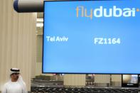 An Emirati journalist awaits a flyDubai flight from Tel Aviv, Israel, at Dubai International Airport's Terminal 3 in Dubai, United Arab Emirates, Thursday, Nov. 26, 2020. The low-cost carrier flyDubai began regular flights to Tel Aviv on Thursday, the latest sign of the normalization deal between the United Arab Emirates and Israel. (AP Photo/Jon Gambrell)