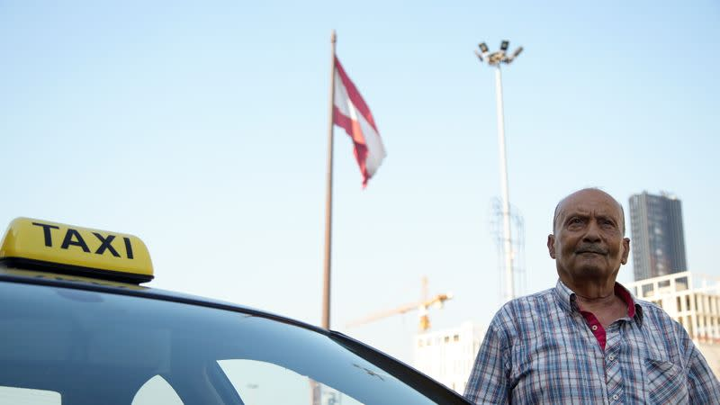 Lebanese flag flutters as Zakaria Ghalayeeni, 76-year-old Lebanese taxi driver, stands near his car at Martyrs' Square in downtown Beirut