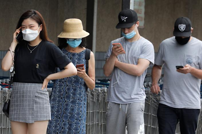 FILE PHOTO: People wear protective face masks outside at a shopping plaza after New Jersey Governor Phil Murphy said he would sign an executive order requiring people to wear face coverings outdoors to prevent a resurgence of the coronavirus disease (COVID-19), in Edgewater, New Jersey, U.S., July 8, 2020. REUTERS/Mike Segar
