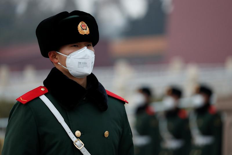 A paramilitary officer wearing a face masks stands guard at the Tiananmen Gate, as the country is hit by an outbreak of the new coronavirus, in Beijing, China January 27, 2020. REUTERS/Carlos Garcia Rawlins