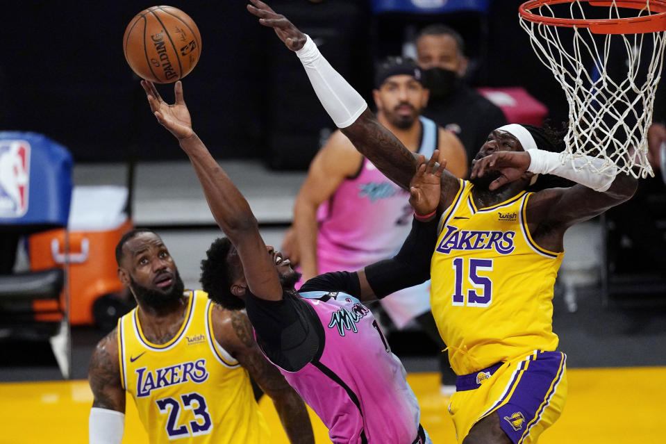 Miami Heat center Bam Adebayo, center, shoots as Los Angeles Lakers forward LeBron James, left, and center Montrezl Harrell defend during the first half of an NBA basketball game Saturday, Feb. 20, 2021, in Los Angeles. (AP Photo/Mark J. Terrill)