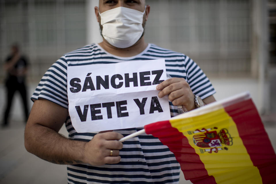 """A man holds a Spanish flag and banner reading in Spanish: """"Sanchez go away"""" during a protest against the Spanish government amid the lockdown to prevent the spread of coronavirus in Alcorcon, Spain, Friday, May 22, 2020. The Spanish government is allowing Madrid and Barcelona to ease their lockdown measures, which were introduced to fight the coronavirus pandemic. (AP Photo/Manu Fernandez)"""