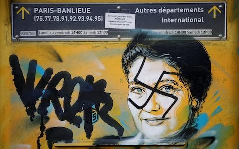 A vandalised mailbox with a swastika covering a portrait of the late Holocaust survivor and renowned French politician Simone Veil is seen before its renovation in Paris - Credit: BENOIT TESSIER/REUTERS