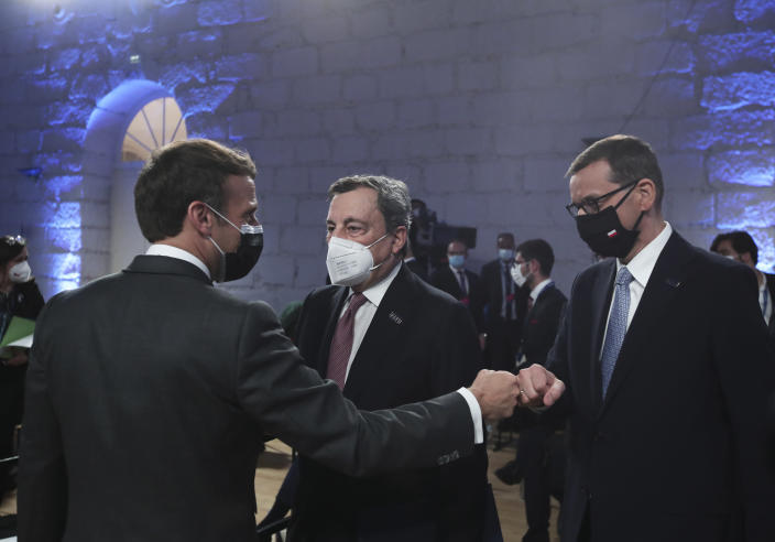 French President Emmanuel Macron, left, fist bumps Poland's Prime Minister Mateusz Morawiecki during the opening ceremony of an EU summit at the Alfandega do Porto Congress Center in Porto, Portugal, Friday, May 7, 2021. European Union leaders are meeting for a summit in Portugal on Friday, sending a signal they see the threat from COVID-19 on their continent as waning amid a quickening vaccine rollout. Their talks hope to repair some of the damage the coronavirus has caused in the bloc, in such areas as welfare and employment. (AP Photo/Luis Vieira, Pool)