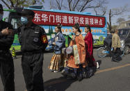 Residents in traditional costumes pass a bus offering free coronavirus vaccinations at an entrance to the Forbidden City in Beijing on Wednesday, April 14, 2021. China's success at controlling the outbreak has resulted in a population that has seemed almost reluctant to get vaccinated. Now it is accelerating its inoculation campaign by offering incentives — free eggs, store coupons and discounts on groceries and merchandise — to those getting a shot. (AP Photo/Ng Han Guan)