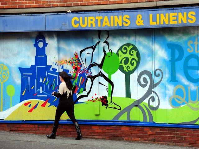 A woman walks past closed shops in Derby city centre (Rui Vieira/PA)